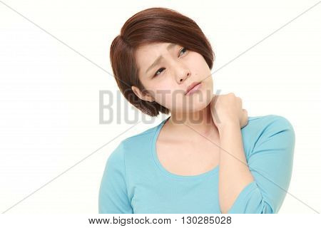 portrait of young Japanese woman suffers from neck ache on white background