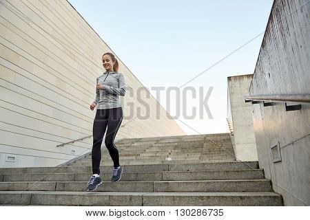 fitness, sport, people and lifestyle concept - happy sporty woman running downstairs in city