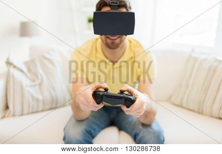 3d technology, virtual reality, gaming, entertainment and people concept - close up of happy young man with virtual reality headset or 3d glasses playing video game with controller gamepad at home