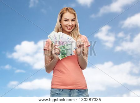 money, finances, investment, saving and people concept - happy young woman with euro cash money over blue sky and clouds background