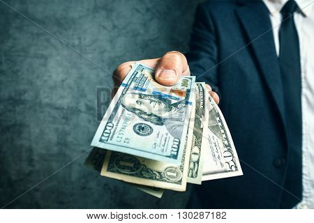 Businessman from bank offering money loan in USA dollar banknotes selective focus.