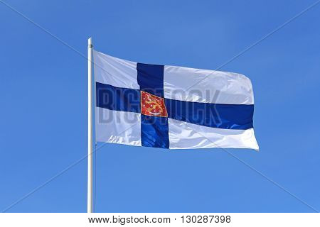 Finland State Flag with Finnish National Coat of Arms against blue sky.