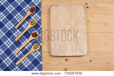 Tablecloth wooden spoon cutboard on wood textured background
