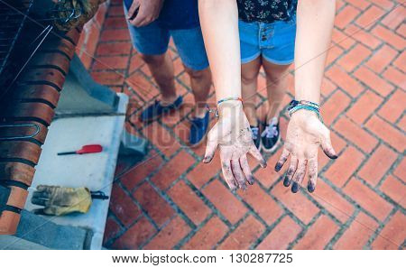View from above of unrecognizable young woman showing her hands dirty of barbecue coal