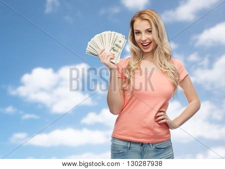 money, finances, investment, saving and people concept - happy young woman with dollar cash money over blue sky and clouds background