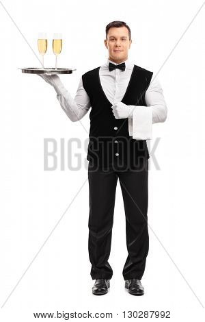 Full length portrait of a young waiter holding a tray with two glasses of white wine isolated on white background