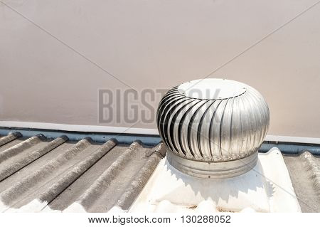 Silver spinning roof ventilator on roof house