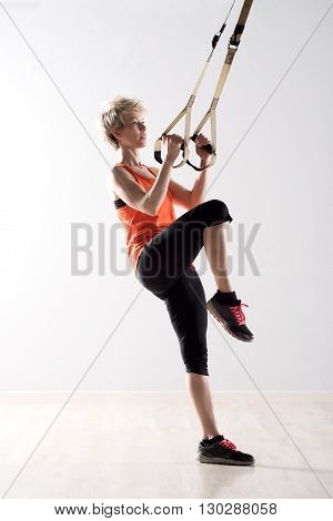 Woman Lifting Leg And Pulling On Exercise Rings