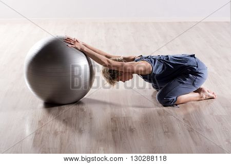 Woman Stretching Shoulders With Fitness Ball