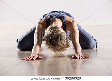 Woman With Head Down While Stretching Hip Muscles