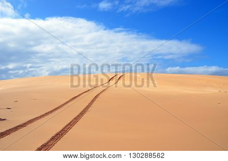 Vehicle tracks over a remote, deserted sand dune.