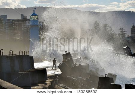 Silhouette of man and dog being sprayed by a big wave on a breakwater near a lighthouse in Wollongong Harbour, Australia