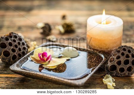 Bowl of beautiful orchid with candle, studio shot