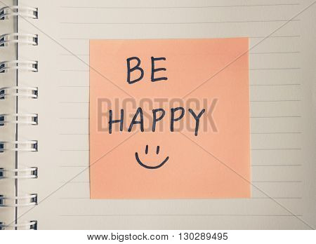 Be happy hand writing and hand draw smiley message on paper colored filter effect