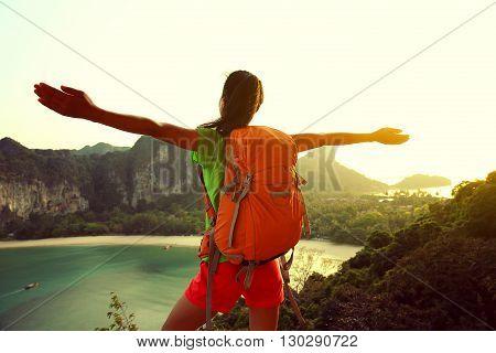 cheering young woman backpacker hiking on seaside mountain