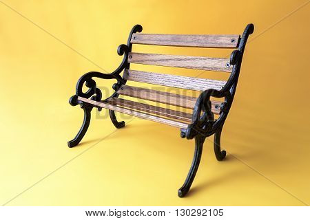 antique small wooden bench on yellow background