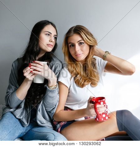 Two young beautiful girls laughing and posing with cups and inhale the aroma of drinks in the bedroom sitting on the bed in the morning.Fresh style life style.