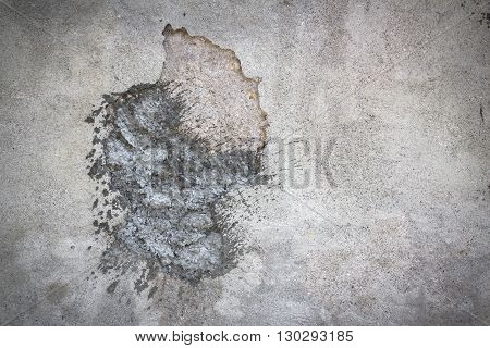 Hole in the wall filled with concrete patch.