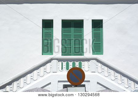 Traditional green window shutters over whitewashed facade Tangier Morocco