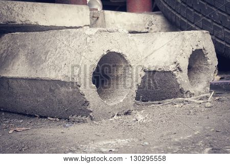 Two abandoned hexagon concrete piles on dirty ground floor selective focus (vintage effect)