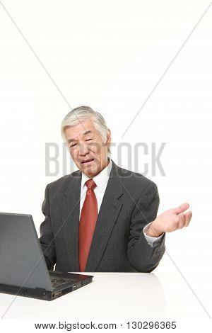 senior Japanese businessman using computer looking confused