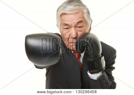 portrait of senior Japanese businessman throws a right straight on white background