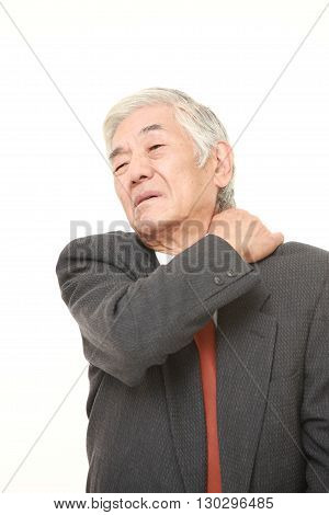 portrait of senior Japanese businessman suffers from neck ache on white background