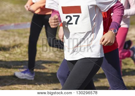 Junior athletic runners on a cross country race. Outdoor circuit. Horizontal