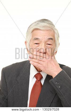 portrait of senior Japanese businessman making the speak no evil gesture on white background