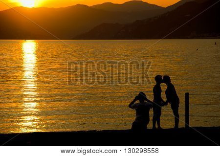 Man And Woman Whiile Kissing On Sestri Levante Beach At Sunset