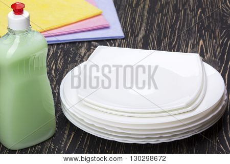 rags, dishes and a bottle of detergent on wooden background