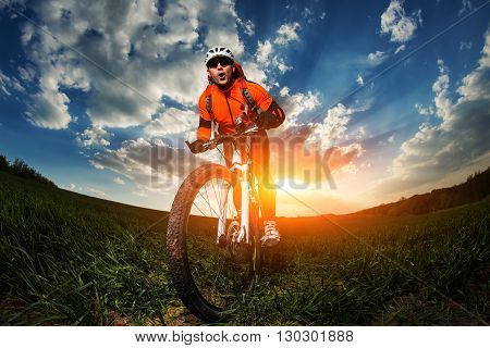 Low, wide angle portrait against blue sky of mountain biker. Cyclist in red sport equipment, helmet and sunglases