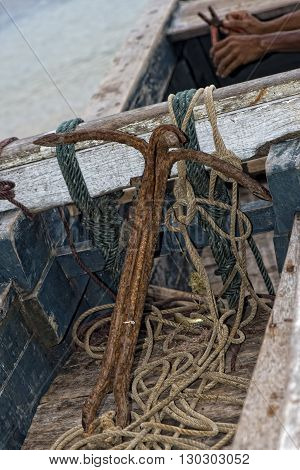 Old rugged anchor on fisherman boat close up