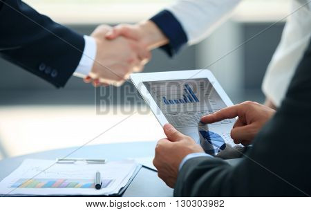 Business associates shaking hands in office at the end of meeting