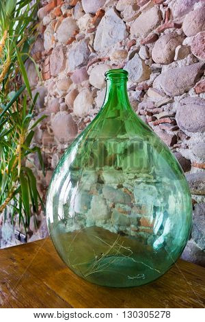 fragment of a room interior with a glass vase a closeup and a stone wall