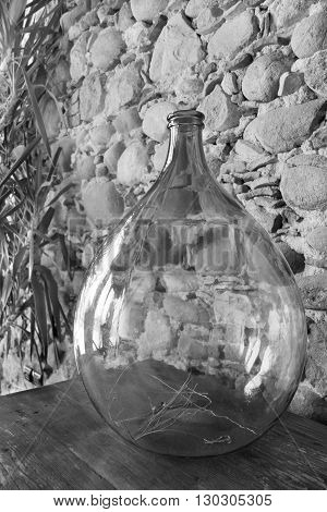 fragment of a room interior with a glass vase a closeup and a stone wall of monochrome tone