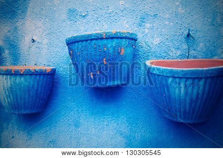 empty three flowerpot in retro style are located separately on the plastered wall closeup for vintage interior