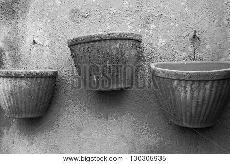 empty three flowerpot in retro style are located separately on the plastered wall closeup for vintage interior of monochrome tone