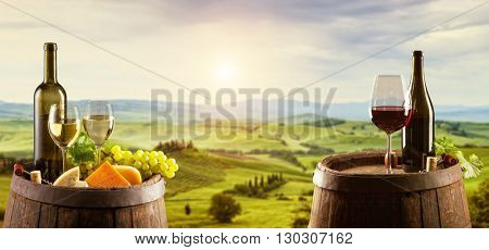 White and red wine with wooden barrel on vineyard in Tuscany, Italy