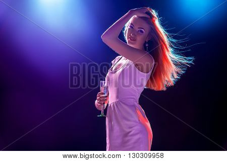 Party, holidays, celebration, nightlife and people concept - smiling young beautiful girl dancing in club
