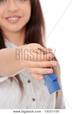 Young businesswoman holding house shaped key chain, isolated on white background