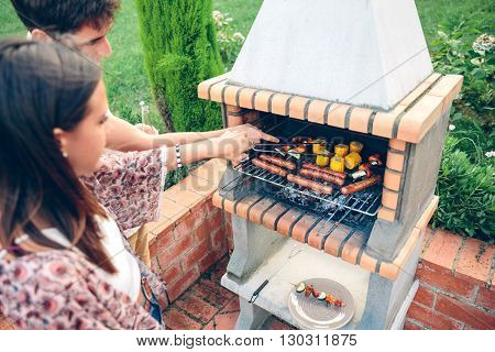 Young friends cooking corn, sausages and vegetable skewers in a barbecue on summer party