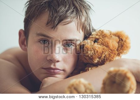 Teenage Boy Snuggling With Brown Teddy Bear