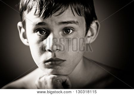 Worried Teenage Boy With Head Resting On Chin