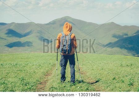 Unrecognizable hiker young man with backpack and trekking poles walking on path in the mountains in summer outdoor rear view