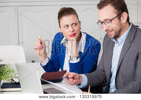 Businessman laughing at the meeting. Businesswoman doesn't like his sense of humor.