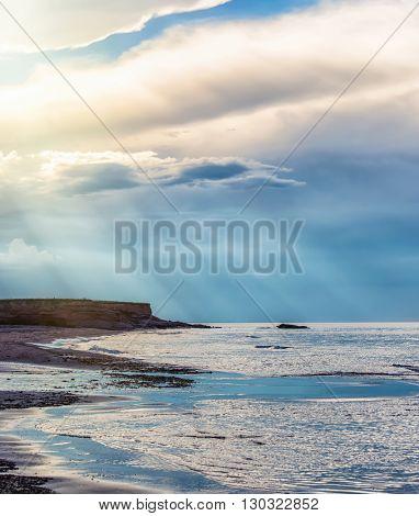 Sunbeams break through the evening clouds on a Prince Edward Island beach.