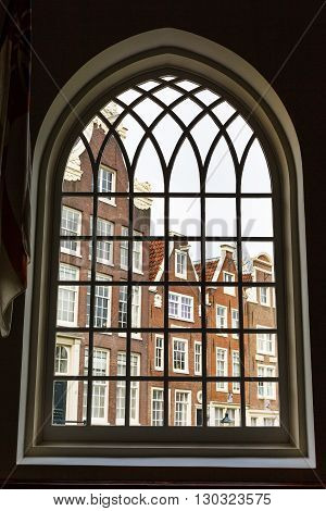 Window view of Begijnhof courtyard with historic Holland houses in Amsterdam, Netherlands