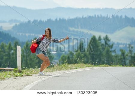 Pretty young woman hitchhiking along the road