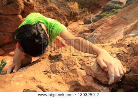 young woman rock climber climbing at mountain rock